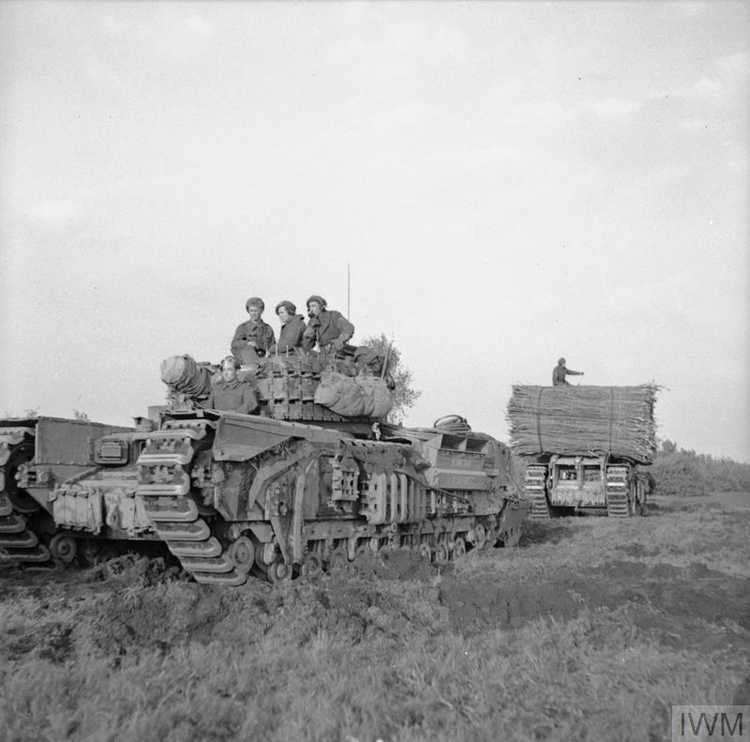 Churchill AVRE towing a sled with fascines, and another carrying a fascine, moving up for 53rd Division's attack west of Oss in Holland, 23 October 1944. Imperial War Museum